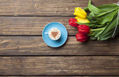 Cappuccino with heart shape and bouquet of tulips — Stok fotoğraf