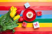 Cup of cappuccino with heart shape and bouquet of tulips — Foto de Stock