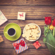 Cup of coffee and gift around with flowers — Stock Photo #70247319