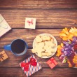 Cup of coffee and gift around with flowers — Stock Photo #70247467