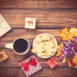 Cup of coffee and gift around with flowers — Stock Photo #70247911