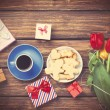 Cup of coffee and gift around with flowers — Stock Photo #70248131