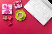 Cup of coffee and gift near computer — Stock Photo