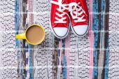 Cup of cappuccino and red gumshoes — Stock Photo