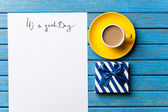 Gift and paper with Good day inscription — Stock Photo