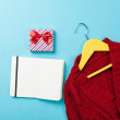 Gift box and notebook near hanger with sweater — Stock Photo #71483789