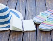 Notebook and hat with flip flops — Stock Photo