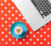 Cappuccino with heart shape and laptop — Stock Photo