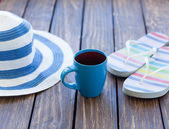 Cup of coffee and hat with flip flops — Stock Photo