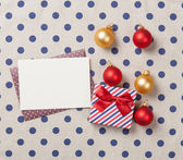 Gift and envelope with christmas boubles — Stock Photo