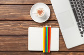 Cappuccino and notebook near laptop — Stock Photo