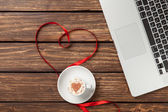 Cappuccino and laptop with red ribbon — Stock Photo