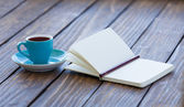Cup of coffee and notebook with pencil — Stock Photo