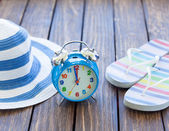 Alarm clock and hat with flip flops — Stock Photo