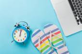 Alarm clock with flip flops near laptop — Stock Photo