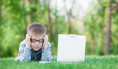 Young sad boy with laptop computer — Stock Photo
