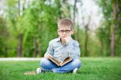 Sad boy with book on green grass — Stok fotoğraf