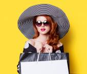 Girl in dress and hat with bags — Stock Photo