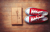 Red gumshoes and package on wooden table. — Stock Photo