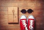 Gumshoes with sunglasses and package — Stock Photo