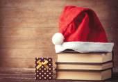Santas hat over books near gift box — Stock Photo