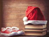 Santas hat over books near red gumshoes — Stock Photo
