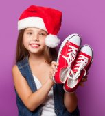 Girl in red Santas hat with gumshoes — Stock Photo