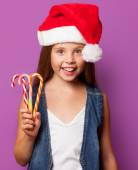 Girl in red Santas hat with candy — Stock Photo