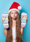 Girl in Santas hat with flip flops — Stock Photo