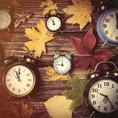 Autumn leavesand alarm clock — Stock Photo