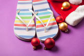 Santas hat and flip flops with balls — Stock Photo
