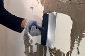 O processo de aplicação de uma massa branca na parede de concreto cinzento — Fotografia Stock