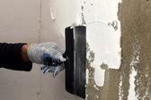 El proceso de la aplicación de una masilla blanca en la pared de concreto gris — Foto de Stock