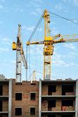 Byggandet av den nya tegelbyggnaden med upplyftande kranen — Stockfoto