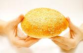Wheaten roll in hands — Stock Photo