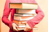A large number of books in the hands  — Stock Photo