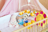 Various soft toys in the cot with orange linen — Stock Photo
