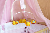 Toy carousel on the cot with orange linen — Stock Photo