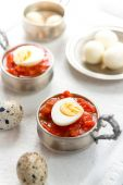 Hard boiled quail eggs with tomato sauce — Stock Photo