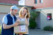 Young attractive woman phoning during a delivery — Stock Photo