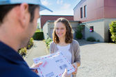 Delivery man handing over a registered letter — Stock Photo