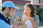 Young attractive woman angry against delivery man — Stock Photo