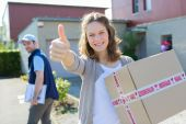 Young attractive woman happy to receive parcel — Stock Photo