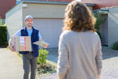 Young attractive delivery man on his way to customer — Stock Photo