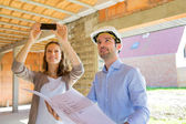 Young woman and architect on construction site  — Stock Photo