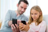 Father and his blond daughter using mobile — Stock Photo