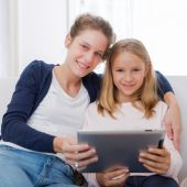 Attractive woman and little sister using tablet — Stock Photo