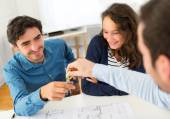 Real estate handing over keys to couple — Stock Photo