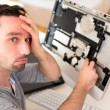 Young attractive man trying to repair computer — Stock Photo #53743333