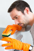 Young attractive man cleaning his flat — Stock Photo
